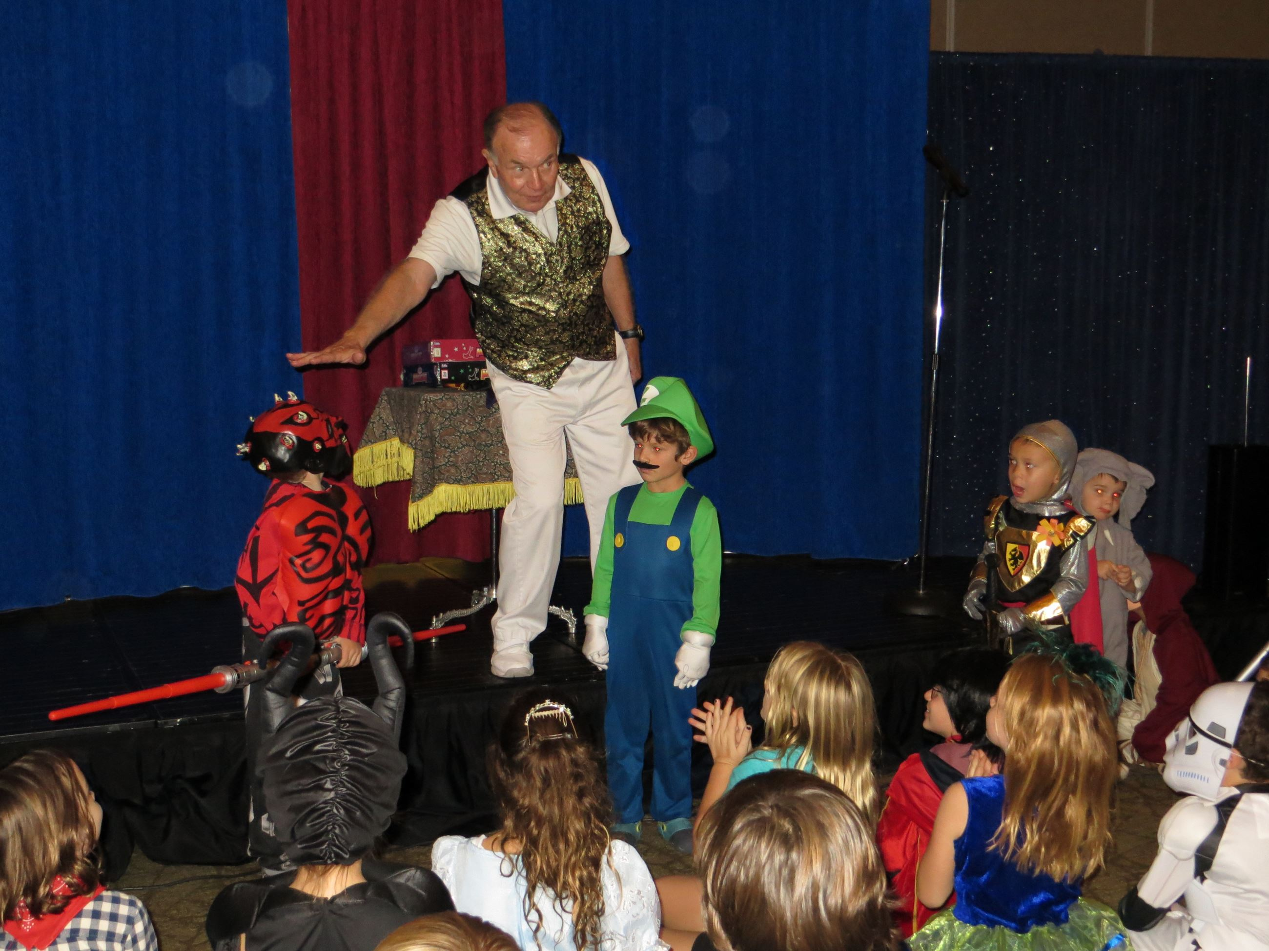 Magician on Stage with 2 kids in costume