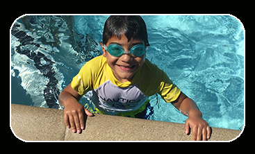 Young smiling boy wearing goggles on edge of pool