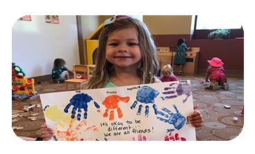 "Preschool Girl holding up sign with handprints and 'we're all friends"" message"