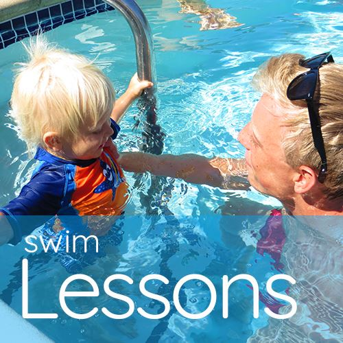 Swim Instructor Teaching toddler how to swim in pool