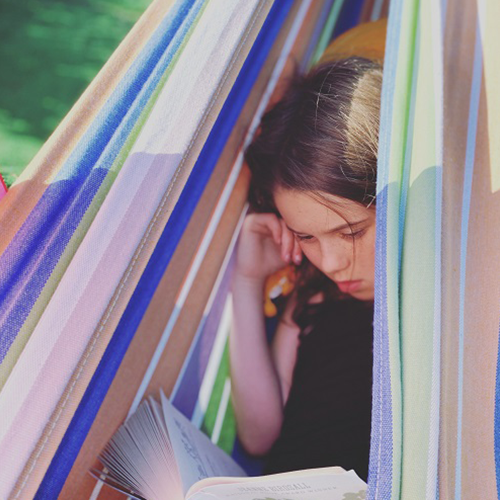 Girl reading a book in a colorful striped canopy tent in the outdoors.